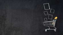 Shopping Cart And Products On Chalkboard. Shop Trolley At Supermarket As Sale, Discount, Shopaholism Concept With Copy Space Left For Text Or Design. Top View Or Flat Lay.