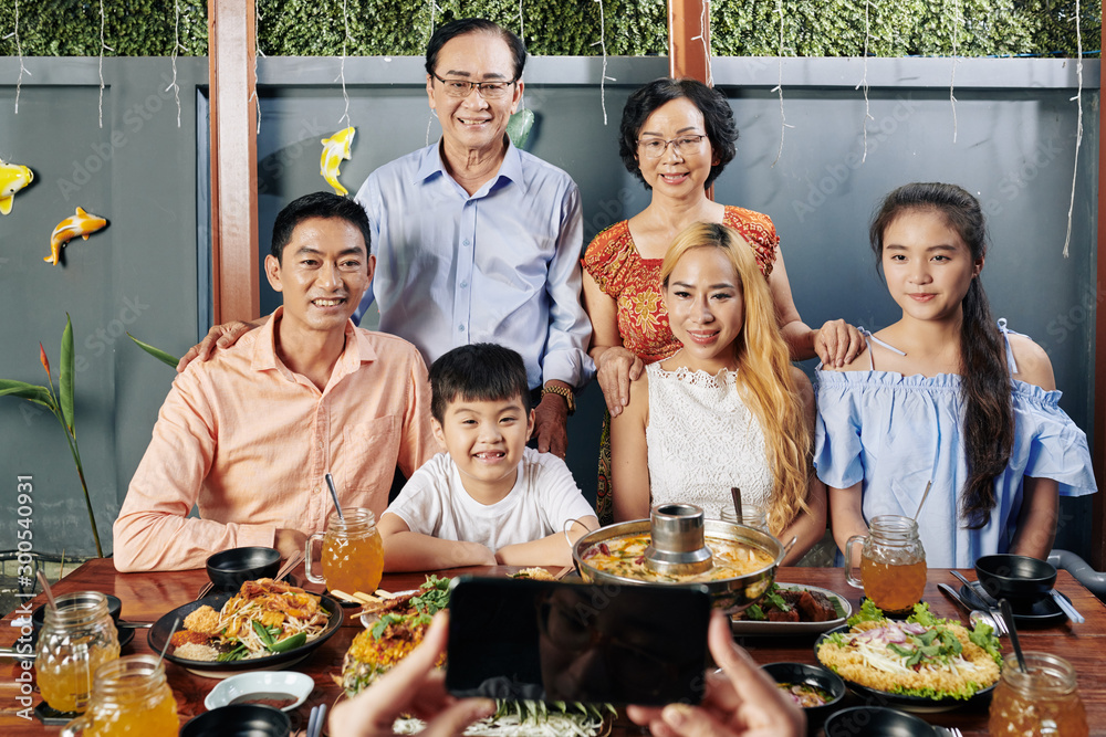 Fototapety, obrazy: Happy big Vietnamese family posing at big dinner table for photo on smartphone