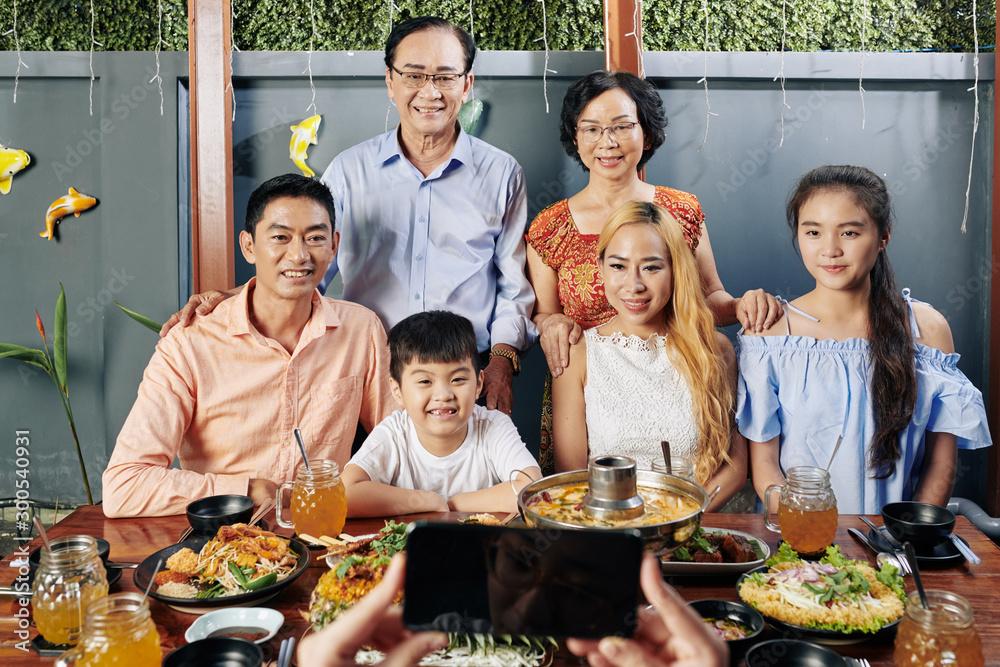 Fototapeta Happy big Vietnamese family posing at big dinner table for photo on smartphone