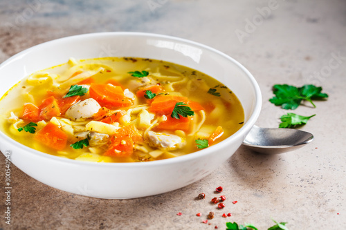Obraz na plátně Chicken soup with noodles, parsley and vegetables in a white plate