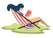 Woman On Beach Lounger And Reading Book With Martini Cocktail