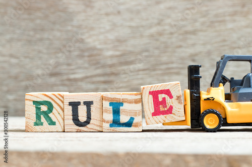 Toy forklift hold letter block e to complete word rule on wood background Wallpaper Mural