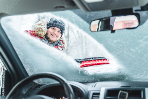 Fotografía  cleaning car after snow storm smiling man with brush