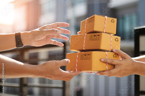 Obraz Hands of customer receiving a cardboard boxes parcel from delivery man in the morning, delivery service concept - fototapety do salonu