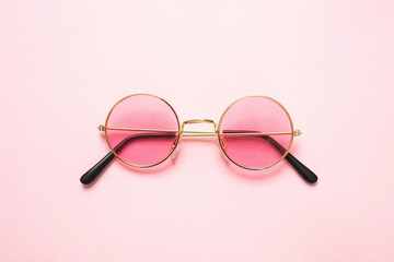Golden frame sunglasses with pink lens on pink background, top view