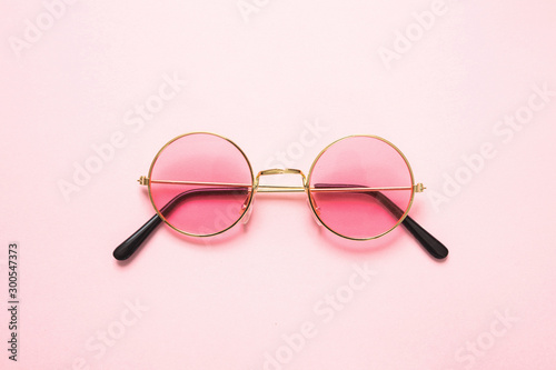 Foto Golden frame sunglasses with pink lens on pink background, top view