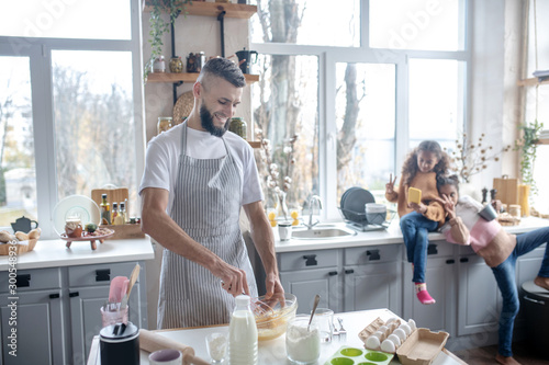 Fotomural Bearded man wearing apron cooking pie for their daughters