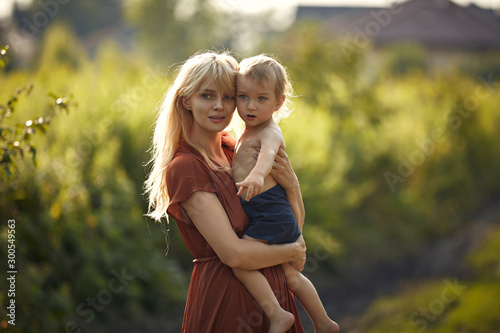 Fotografie, Tablou  Pretty young mother carrying her beloved son