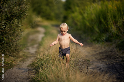 Cute little boy waling on a country path