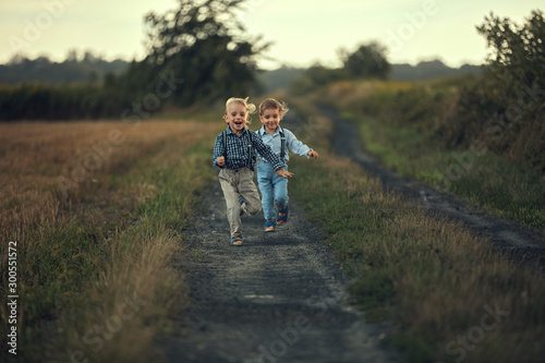 Two adorable boys running on the country road