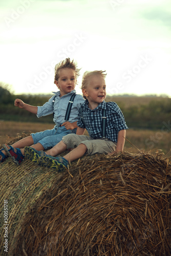 Two cute brothers leaning on the sheaf