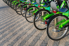 Many Black And Green Bicycles In A Row. Trends In Bicycle-making Industry. Group Of Cycles. Bike Stand On Parking For Rent. Eco Friendly Transportation Concept. City Eco-friendly Transportation