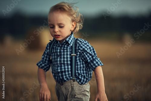 Photo sur Toile Artiste KB Closeup portrait of a little blond boy running on the wheat field