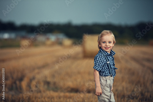 Portrait of a cheerful child posing on the corn field