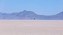 Car Speeding On A Playa Of Alvord Lake, South Oregon. A Trace Of Dust Rises Behind A Car Driving Fast On Hot Day. Warm Air Creates A Mirage Of A Water On A Surface Of A Dried Lake