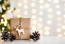 Close Up Of Gift Box And Fir Cones Near Decorated Christmas Tree Over White Wall Background With Lights