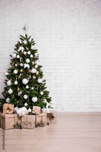 christmas and new year background - christmas tree and gift boxes over white brick wall with copy space