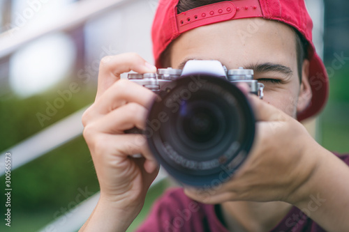 Teenage boy taking photos outdoors Wallpaper Mural