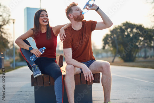 Obraz Modern couple making pause in an urban park during jogging / exercise. - fototapety do salonu