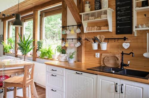 Obraz Interior of kitchen in rustic style with vintage kitchen ware and window. White furniture and wooden decor in bright indoor. Country style. - fototapety do salonu