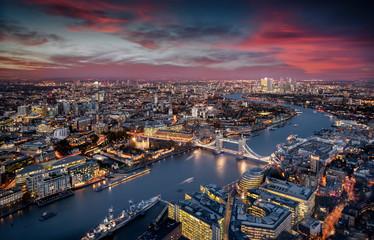 Blick über London: die beleuchtete Skyline von der Tower Brücke entlang der Themse zu den Wolkenkratzern von Canary Wharf am Abend