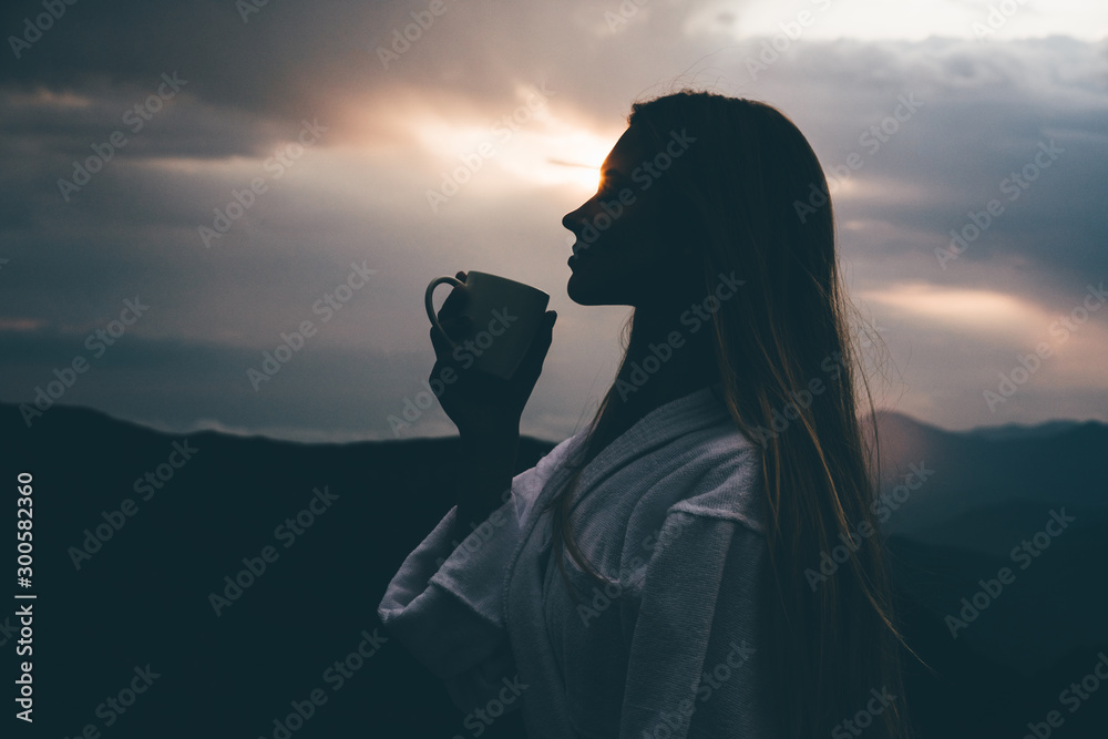 Fototapety, obrazy: Side view woman in SPA bathrobe standing in the beautiful mountain view at the sunset. Travel and healthy lifestyle and beauty outdoors.