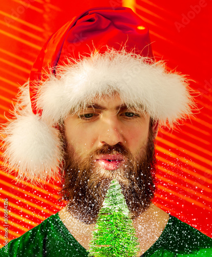 Tela  a man in a fluffy Santa hat with a real beard blows snow away from a Christmas t