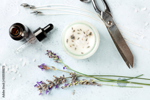 Handmade lavender scented candle with essential oil, flowers, wax, wicks, and scissors, flatlay, shot from the top Canvas Print