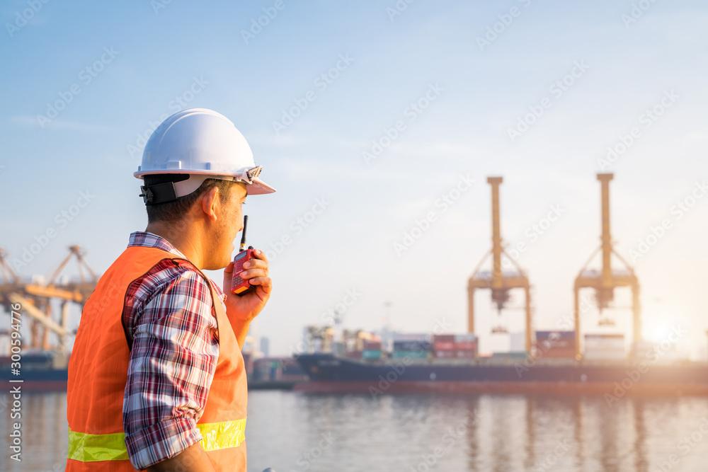 Fototapeta worker use radio communication with large crane site background