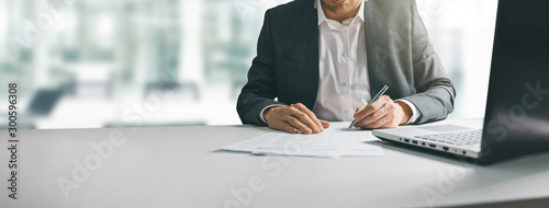 Cuadros en Lienzo young man in suit writing business papers at desk in modern coworking office