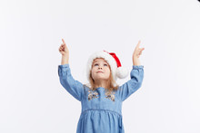 Happy Smiling Child Girl In Santa Hat And Blue Dress Having Fun On A Red Isolated Background. Points With Hands Up, Empty Area For Text. Merry Christmas. Happy New Year