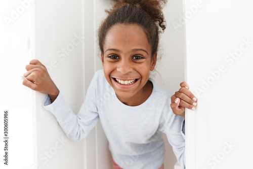 Fotomural  Image of african american little girl playing hide and seek in closet