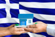 Greece Real Estate Concept. Man And Woman Holding Miniature House In Hands. Citizenship Theme And National Flag On Background.