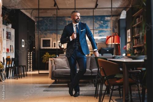 Fotografía  Stylish bearded man in a suit standing in modern office