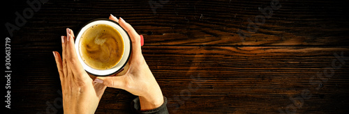 Dark mood wooden desk of free space for your text or product.Woman hands holding cup of coffee in cafe interio. Dark mood photo with shadows and flat lay. Copy space. Aerial view. Winter time.