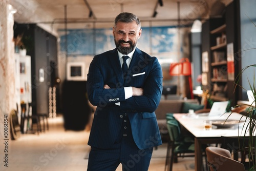 Valokuva  Stylish bearded man in a suit standing in modern office