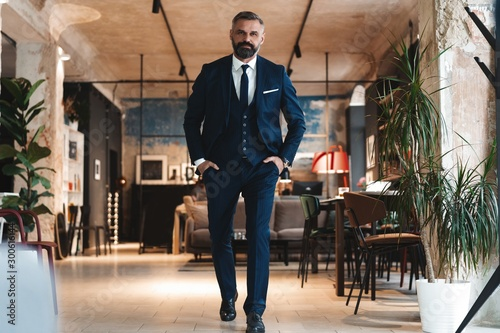 Pinturas sobre lienzo  Stylish bearded man in a suit standing in modern office