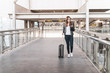 Young woman walking inside the airport with her luggage and her mobile phone. Concept of travel and vacation.
