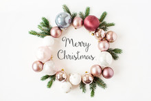 """Christmas / New Year Holiday Composition. Quote """"Merry Christmas"""" In Frame Wreath With Christmas Baubles, Balls And Fir Branches On White Background. Flat Lay, Top View Festive Concept."""