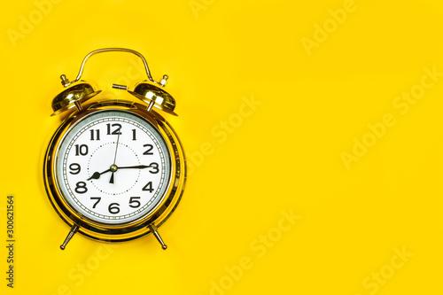 Reloj dorado con agujas despertador vintage sobre fondo amarillo brillante Poster Mural XXL