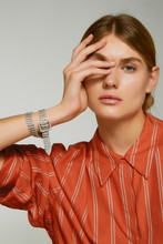 Close-up Shot Of A Blonde European Lady In A Terracotta Striped Shirt And A Crystal Rhinestone Bracelet With A Belt Buckle Twisted Around Her Wrist Twice. The Photo Is Made On The Gray Background.