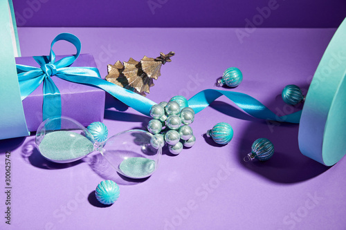 Fotobehang Londen Christmas decoration and hourglass scattered from blue gift box on purple background