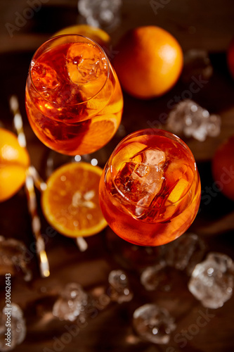 top view of Aperol Spritz in glasses, oranges and ice cubes