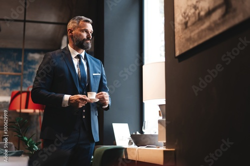 Confident man in smart casual wear holding coffee cup at his working place in office