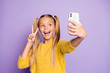 canvas print picture - Portrait of funny funky child piggytails ponytails enjoy trip take selfie make v-signs wear stylish yellow pullover isolated over purple color background