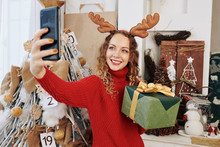 Beautiful Smiling Young Woman In Reindeer Antlers Taking Photo With Christmas Gift On Her Smartphone