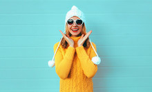 Winter Portrait Happy Surprised Young Woman Wearing Yellow Knitted Sweater And White Hat With Pom Pom, Heart Shaped Sunglasses On Blue Wall Background