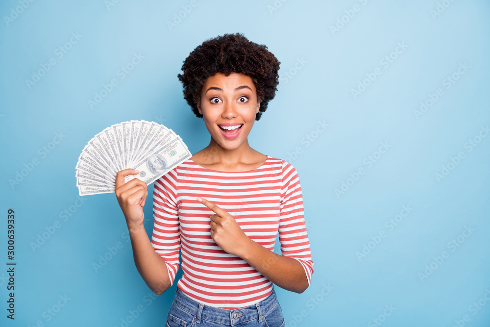 Fototapety, obrazy: Photo of pretty sweet stunned girlfriend with astonishment on face smiling toothily pointing at fan of money she holds in striped shirt jeans denim isolated pastel blue color background