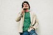 Outdoor portrait of young man talking on mobile phone with his friend. Happy male with curly hair resting outside making a call on his cell phone in the city street. Lifestyle, people