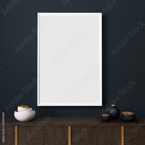 Picture mockup with white vertical frame on dark blue wall. Stylish dark interior with decor and wooden cupboard and blanket picture. Poster mockup. Minimalist modern interior design. 3D illustration.